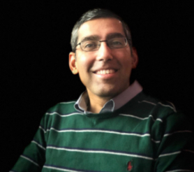 Medium close up photo of a smiling 40 year old Goan Indian man wearing a green and white stripped collared sweater and glasses.