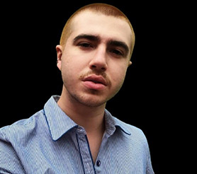 Medium close up photo of young adult Caucasian person wearing a collared blue and white stripped shirt.