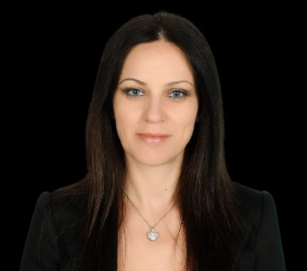 A smiling Albanian blue eyed woman with dark brown hair wearing a black blazer and heart shaped necklace.
